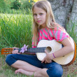 Girl with guitar by tree — Stock Photo #12326238