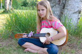 Girl with guitar by tree — Stock Photo