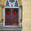 Christmas wreaths on church door — Stok fotoğraf