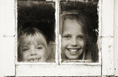 Girls peeking out of window — Stock Photo