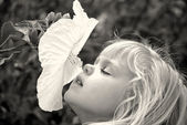 Girl sniffing a hibiscus — Stock Photo