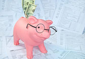 Piggy bank on income tax forms — Stock Photo