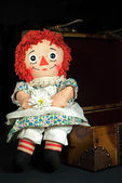 Old rag doll on a suitcase — Photo