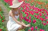 Beautiful young woman in tulips — Stock Photo