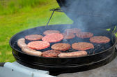 Grilling hamburgers and bratwurst — Stock Photo