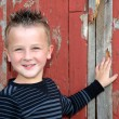 Smiling young boy by barn — Stock Photo
