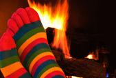 полосатые ноги носки у камина — Стоковое фото