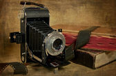 Vintage bellows camera with books — Stock Photo
