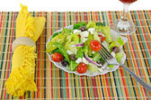Greek salad on bamboo place mat — Stock Photo