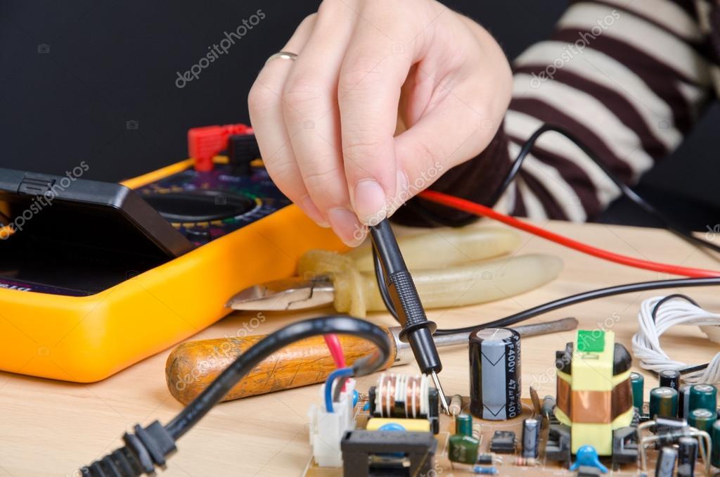 妇女与数字万用表维修线路板