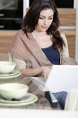 Woman using her laptop in kitchen — Stock Photo