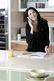 Frau auf ihrem handy in einer küche — Stockfoto