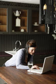 Woman on a laptop in kitchen — Stock Photo