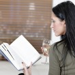 Woman relaxing with a book and wine — Stock Photo