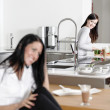 Two friends catching up in the kitchen — Stock Photo