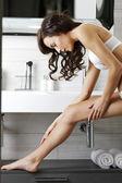 Woman moisturising legs — Stock Photo