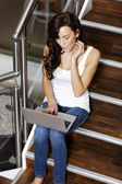 Woman using laptop on staircase — Stock Photo