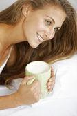 Donna di gustare un caffè a letto — Foto Stock