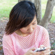 Young women playing with mobile at park — Stockfoto