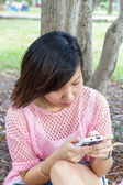 Young women playing with mobile at park — Stock Photo