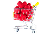 Many red hearts in shopping cart side view — Stock Photo