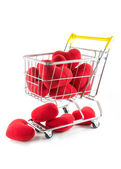 Many red hearts in shopping cart and fall on the floor — Stock Photo