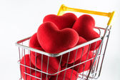 Closeup many red hearts in shopping cart — Stock Photo