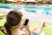 Women play with mobile relaxing on poolside — Stock Photo