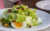 Caesar salad with eggs, bacon on plate — Stock Photo
