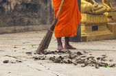 Monk sweeping leaf — Stock Photo
