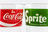 Coca-Cola and Sprite classic logo on empty glass — Stock Photo