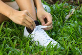 Hands lacing with bootlace the sneaker closeup — Stock Photo
