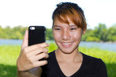 Asian women taking pictures of themselves with a cellphone at public park — Stock Photo