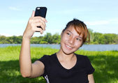 Young women taking pictures of themselves with a cellphone at public park — Stock Photo