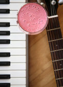 Fresh cold raspberry smoothie, guitar and piano — Stock Photo