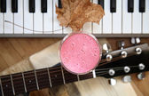 Fresh cold raspberry smoothie, yellow leaf, guitar and piano — Stock Photo
