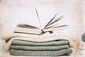 Artwork in retro style, opened book and wool knitting — Stock Photo