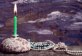 Burning candle, cake, pearls, purple background — Foto Stock
