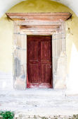 Old woodcarved red door — Stock Photo
