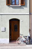 Wall with wooden door, window and bike — Стоковое фото