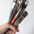 Bunch of stained brushes in woman hand — Stock Photo