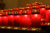 Red burning candles inside a church — Foto Stock