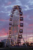 Ferris wheel at amusement park against the red clouds — Stock Photo