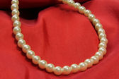 Pearl necklace on red fabric — Stock Photo