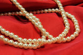 Pearls on red fabric — Stock Photo