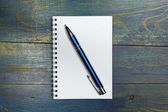 Spiral notebook with pen on old blue wooden table — Stockfoto