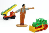 Toy figure of street builder and bulldozer — Stock Photo