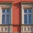 Two windows with ornamental decoration on red wall- Krakow, Poland — Stock Photo