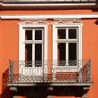 Orange tenement wall with two windows and balcony — Stock Photo