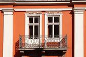 ściany kamienicy pomarańczowy z dwoma oknami i balkonem — Zdjęcie stockowe